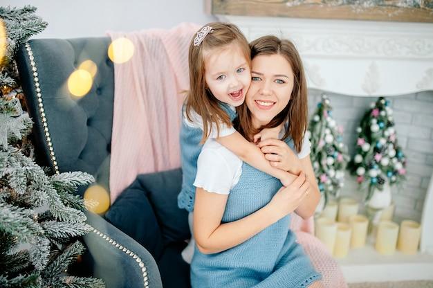 Schöne junge frau und ihre reizend kleine tochter umarmen im gleichen ausstattungslächeln. weihnachtsfeiertage