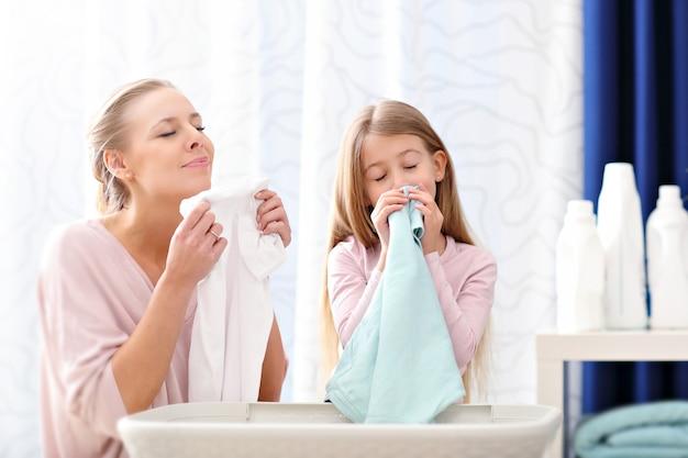 Schöne junge frau und kindermädchen, die spaß beim wäschewaschen zu hause haben