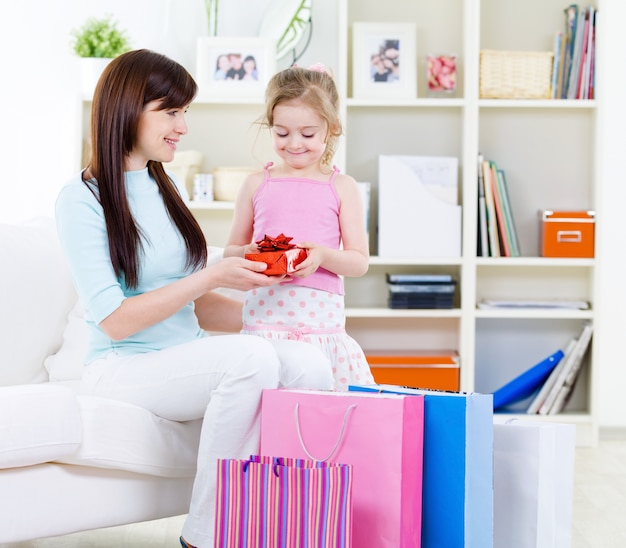 Schöne junge frau und kleine tochter mit geschenk nach dem einkaufen zu hause