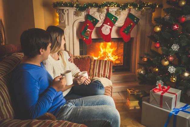Schöne junge frau und mann entspannen am kamin und geschmückten weihnachtsbaum