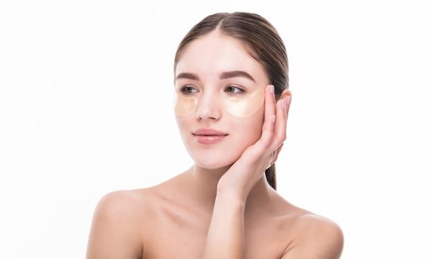 Schöne junge frau verwenden patch auf frischer haut berühren eigenes gesicht. gesichtsbehandlung. kosmetologie.