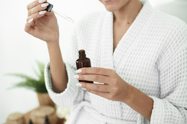 Schöne junge frau verwendet feuchtigkeitscreme anti-aging-serum-behandlung auf ihren händen. beauty body skin care und cosmetic apply concept.