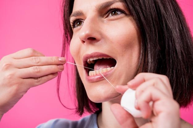 Schöne junge frau verwendet zahnseide auf rosa hintergrund Premium Fotos