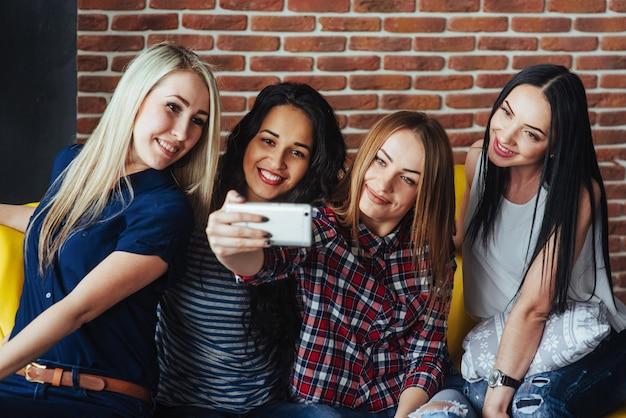 Schöne junge frau vier, die selfie in einem café, mädchen der besten freunde zusammen haben spaß, emotionale lebensstilleute aufwerfend tut