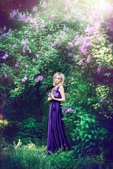 Schöne junge frau von lila blumen umgeben. frau in einem langen kleid mit einem schlitz auf dem hintergrund eines frühlingsgartens mit flieder. konzept von kosmetika und parfums