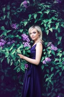 Schöne junge frau von lila blumen umgeben. frau sitzt in einem langen kleid mit einem schlitz auf dem hintergrund eines frühlingsgartens mit flieder