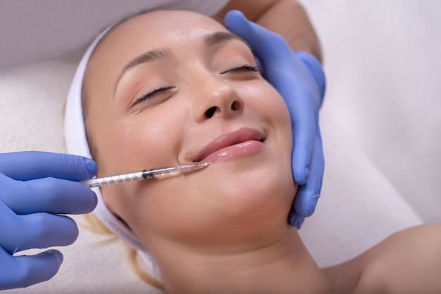 Schöne junge frau während der hautbehandlung mit hyaluronsäure in einer schönheitsklinik