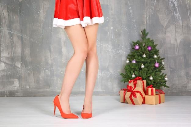 Schöne junge frau, weihnachtsbaum und geschenkboxen gegen schmutzwand