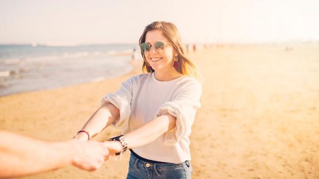 Schöne junge frau, welche die hand ihres freundes am strand hält