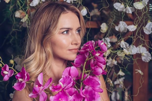 Schöne junge frau, welche die orchideenblume schaut weg hält