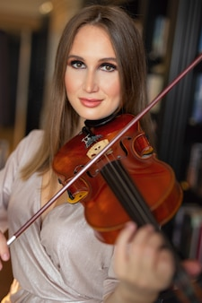 Schöne junge frau, welche die violine spielt
