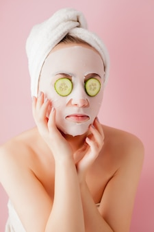 Schöne junge frau wendet eine kosmetische gewebemaske auf ein gesicht mit gurke auf einem rosa an
