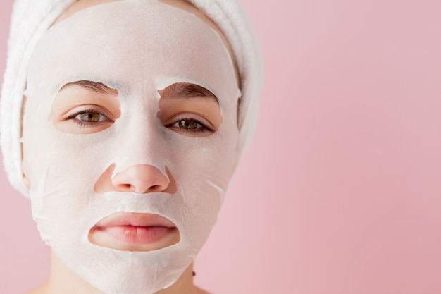 Schöne junge frau wendet eine kosmetische gewebemaske auf einem gesicht auf einem rosa hintergrund an