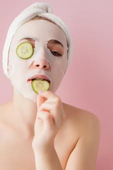 Schöne junge frau wendet eine kosmetische gewebemaske auf einem gesicht mit gurke auf einem rosa hintergrund an.