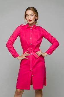 Schöne junge frau wirft für die kamera im rosa kleid auf weißem raum auf