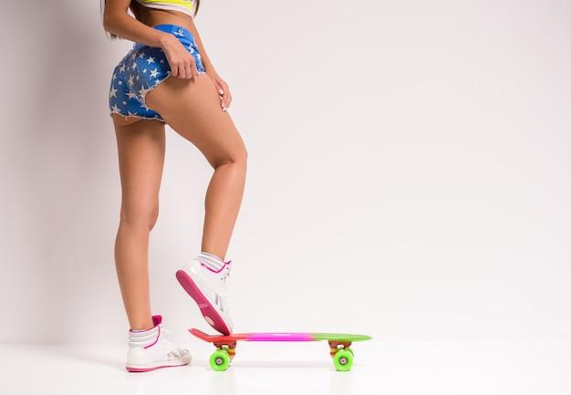 Schöne junge frau wirft mit einem skateboard auf.