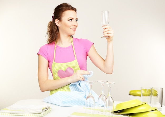 Schöne junge frau wischt saubere utensilien in der küche auf grau ab