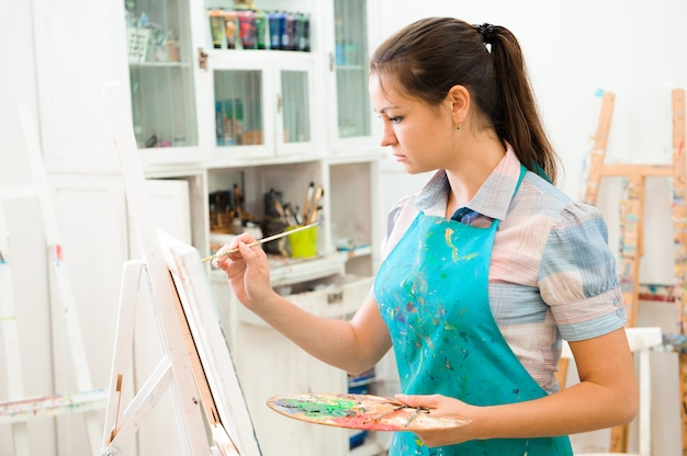 Schöne junge frau zeichnet ein bild malt auf kunststunde.