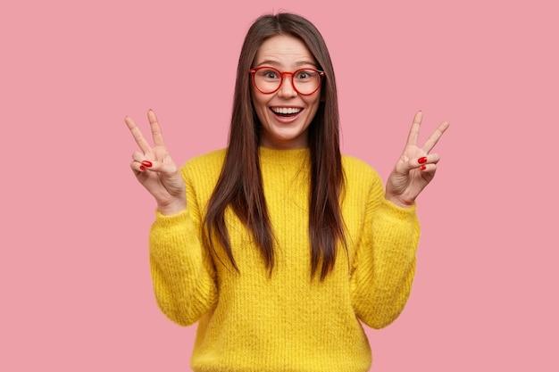 Schöne junge frau zeigt friedenszeichen mit beiden händen, lächelt breit, trägt optische brille, gelbe kleidung, posiert vor rosa hintergrund, hat freude