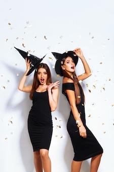 Schöne junge frauen als hexe für halloween-party verkleidet