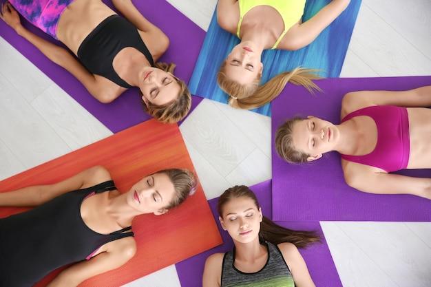 Schöne junge frauen, die auf yogamatten im fitnessstudio liegen
