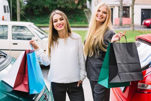 Schöne junge frauen, die außerhalb der straße in der hand halten einkaufstaschen stehen