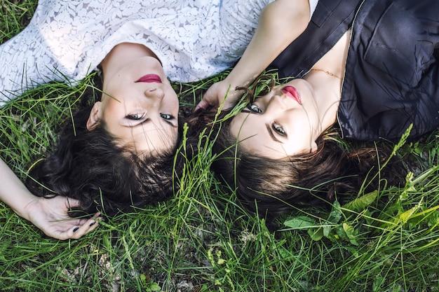 Schöne junge frauen, die glücklich lächelnd im gras in der sommernahaufnahme lächeln