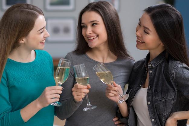 Schöne junge frauen, die mit champagnergläsern feiern
