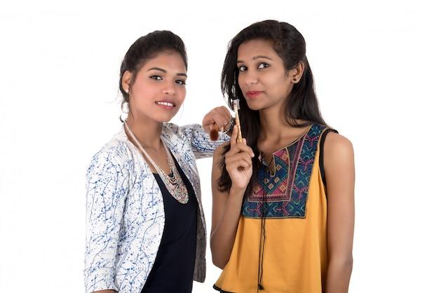 Schöne junge frauen, die mit make-up-pinseln lokalisiert auf weiß genießen
