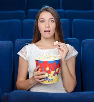 Schöne junge frauen, die popcorn essen.