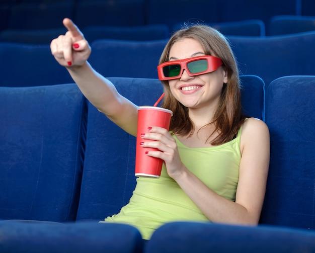 Schöne junge frauen, die soda beim aufpassen des films trinken