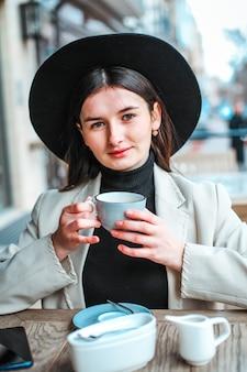 Schöne junge frauen, die tee im restaurant trinken