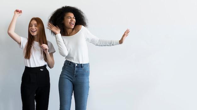 Schöne junge frauen, die zusammen tanzen