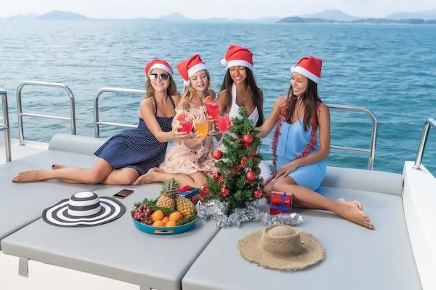 Schöne junge frauen feiern weihnachten in hüten mit getränken und früchten auf yacht