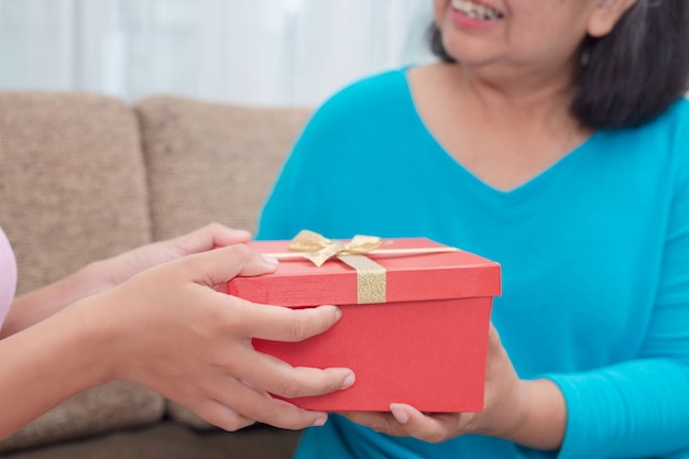 Schöne junge frauen geben den müttern geschenke.