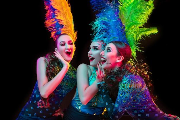Schöne junge frauen im karneval, stilvolles maskenkostüm mit federn an schwarzer wand im neonlicht
