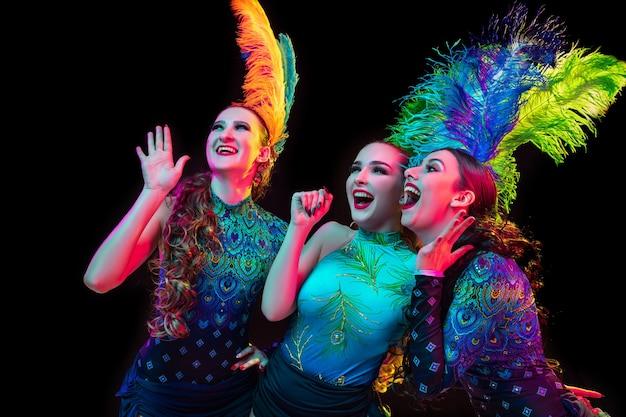 Schöne junge frauen im karneval, stilvolles maskeradenkostüm mit federn auf schwarzem hintergrund im neonlicht.