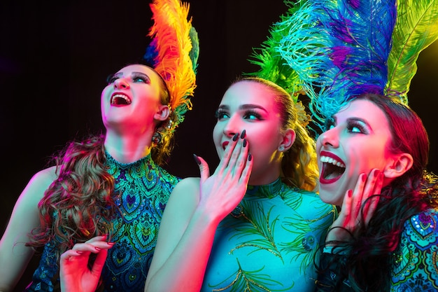 Schöne junge frauen im karneval, stilvolles maskeradenkostüm mit federn auf schwarzer wand im neonlicht