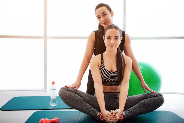 Schöne junge frauen im weißen fitnessraum.