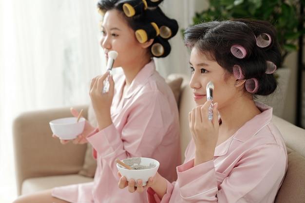 Schöne junge frauen mit lockenwicklern, die eine feuchtigkeitsspendende und porenverfeinernde holzkohle-gesichtsmaske auftragen