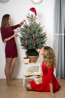 Schöne junge frauen schmücken den weihnachtsbaum