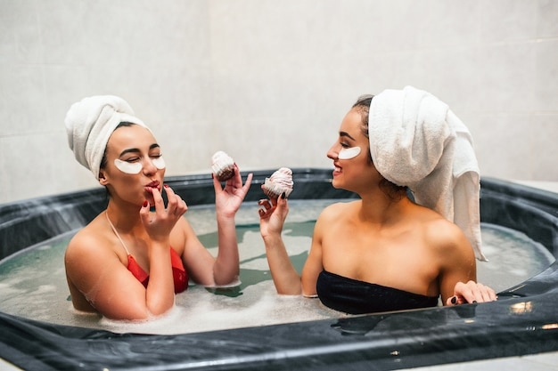 Schöne junge frauen sitzen im hydromassagebad und essen pfannkuchen. sie haben es in händen. asiatisches model leckt sich die finger. frauen haben entspannung und spaß.