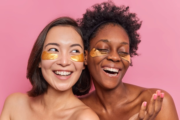 Schöne junge frauen tragen hydrogel-augenklappen nach dem duschen auf und unterziehen sich aufrichtig schönheitsbehandlungen mit freude, verwenden moderne kosmetik oder produkte stehen im innenbereich