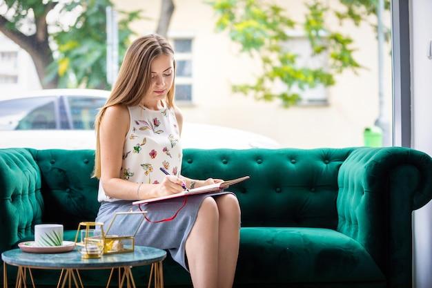 Schöne junge freiberuflerin, die in notizbuch, geschäftsmann-konzept schreibt