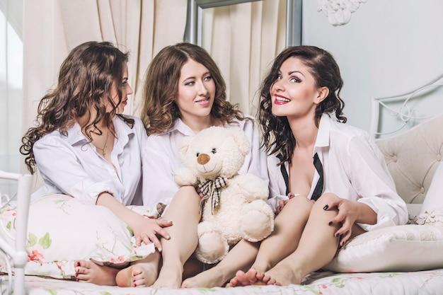 Schöne junge freundinnen, die im schlafzimmer in weißen hemden plaudern