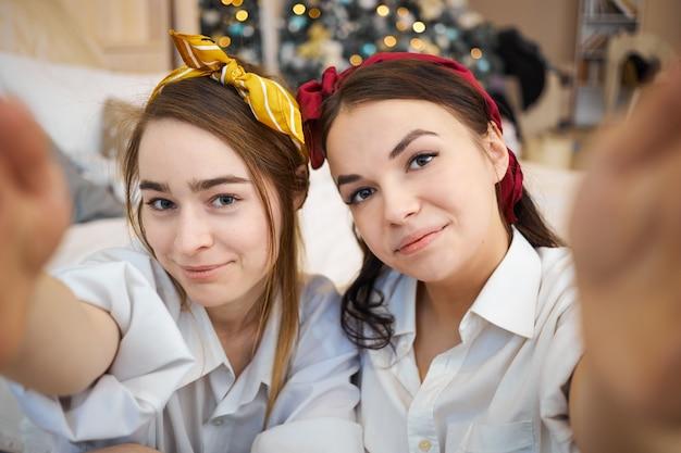 Schöne junge freundinnen, die zu hause zusammen entspannen und selfie nehmen