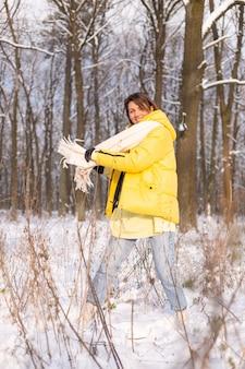 Schöne junge fröhliche frau in einem verschneiten landschaftswinterwald, der spaß hat, freut sich im winter und schnee in der warmen kleidung