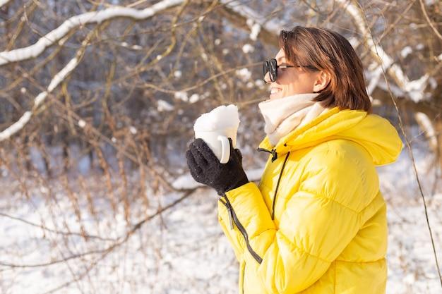 Schöne junge fröhliche frau in einem verschneiten landschaftswinterwald in der sonnenbrille mit einer tasse gefüllt mit schnee, der spaß hat