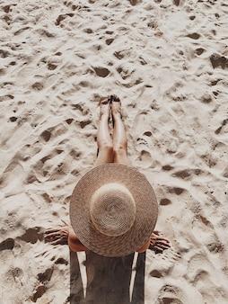 Schöne junge, gebräunte frau mit einem strohhut liegt und entspannt am tropischen strand mit weißem sand, der beine zeigt