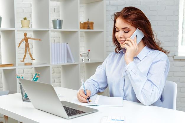 Schöne junge geschäftsfrau benutzt einen smartphone und arbeitet im büro